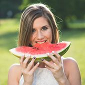 stock photo of watermelon slices  - Pretty happy woman eating slice of juicy red watermelon outdoors in park with shallow depth of field - JPG
