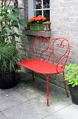 picture of wrought iron  - Red wrought iron bench outside on a garden patio - JPG