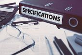 stock photo of peculiar  - Office folder with inscription Specifications on Office Desktop with Office Supplies - JPG