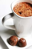 picture of hot-chocolate  - A white mug of hot chocolate with chocolates on the side - JPG