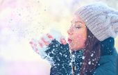 Winter girl blowing snow. Beauty Joyful Teenage Model Girl having fun in winter park. Beautiful youn poster