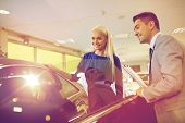 auto business, car sale, consumerism and people concept - happy woman with car dealer in auto show o poster