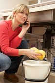 picture of leaked  - Woman Mopping Up Leaking Sink On Phone To Plumber - JPG