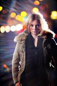 Portrait of young blond woman in parka at night.