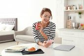 Beautiful Young Woman With Cup Of Coffee And Smartphone At Table. Lazy Morning poster