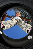 stock photo of tire swing  - Young tomboy girl on tire swing - JPG