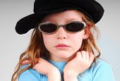 foto of newsboy  - Young girl looking serious in sunglasses and black cap - JPG