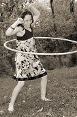 foto of hulahoop  - Young girl having fun with hula hoop outside - JPG