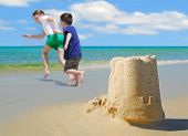 happy children running on beach by sand castle