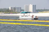 ORANGE BEACH, AL - JUNE 8: Recreational boaters navigate through oil boom draped in Perdido Pass on