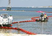 PENSACOLA - JUNE 10:  Oil spill workers clean the beach of Naval Air Station Pensacola, FL as oil wa