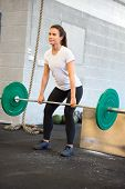 Female Athlete Weightlifting With Barbell In Health Club poster
