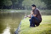 Happy Young Ethnic Father and Son Fishing at the Lake.