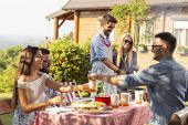 Group Of Friends Making Barbecue In The Backyard And Having Fun On A Sunny Summer Day. Focus On The  poster