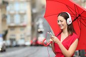 Happy Woman Listening To Music With Phone And Headphones In A Rainy Day In The Street poster
