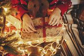 Hands Opening Christmas Gift Box On At Golden Beautiful Christmas Tree With Lights In Festive Room.  poster