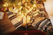 Girl Legs In Stylish Warm Sock Standing With Garland Lights Under Christmas Tree With Presents And G poster