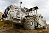 picture of loamy  - huge rotary hoe in wide angle view on construction ground - JPG