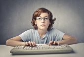 stock photo of virus scan  - Child typing on a computer keyboard - JPG