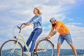 Woman Rides Bicycle Sky Background. How To Learn To Ride Bike As An Adult. Girl Cycling While Boyfri poster