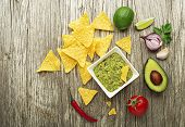 Guacamole Sauce With Fresh Ingredients And Corn Nachos Chips On Wooden Background poster