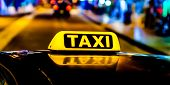 Night Picture Of A Taxi Car. Taxi Sign On The Car Roof Glowing In The Dark poster