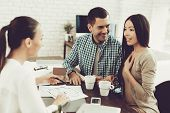 Young Man And Woman With Smiling Realtor In Office. Blueprint On Wooden Desk. Real Estate Concepts.  poster