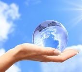 stock photo of world-globe  - Globe in human hand against blue sky - JPG