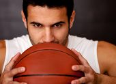 Aggressive male basketball player holding the ball