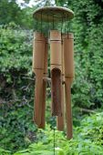 stock photo of windchime  - bamboo wind chimes hanging from roof in garden - JPG