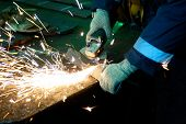 picture of welding  - worker welding metal with sparks at factory - JPG