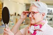 Happy senior woman with new glasses looking in mirror at optician