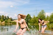 Two happy women having fun in summer at lake, they wearing swimwear