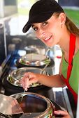 image of ladle  - Female owner of a soup kitchen or a field kitchen stirs with a ladle in the soup - JPG