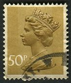 UK-CIRCA 1977: A stamp printed in UK shows image of Elizabeth II is the constitutional monarch of 16