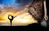 stock photo of natarajasana  - man silhouette doing natarajasana dancer pose on the beach near the fisherman boat at sunset background in Varkala Kerala India - JPG