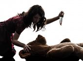 stock photo of serial killer  - one caucasian strange young woman killing her teddy bear  in silhouette white background - JPG