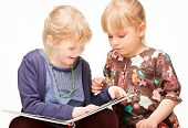 Two cute little girls reading a book