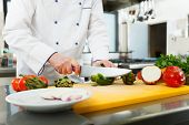 stock photo of chef knife  - Chef preparing vegetables in his kitchen - JPG