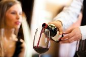 foto of catering service  - Waiter pouring red wine to a woman - JPG