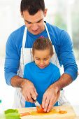loving father teaching little daughter cooking in kitchen