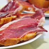 closeup of a some plates with spanish tapas of serrano ham served on sliced bread, on a set table of