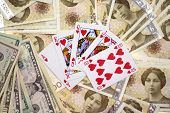 image of derringer pistol  - Money and a royal flush Winning money conceptual shot for playing cards - JPG