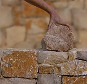 image of stonewalled  - Mason hands working on masonry stone wall stonewall - JPG