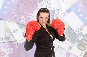 stock photo of troika  - Portrait of a young female entrepreneur wearing boxing gloves - JPG