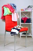 stock photo of slut  - Heap of  clothes on color chair - JPG