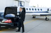 image of luxury cars  - Young businessman getting luggage out of luxury car to get into corporate jet - JPG