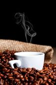 stock photo of steamy  - White steamy cup among coffee beans with burlap sack in the background - JPG