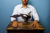 image of taxidermy  - Young man is sitting at a wooden table with a taxidermy magpie in front of him - JPG