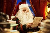 Image of portrait of santa claus reading a christmas letter.
